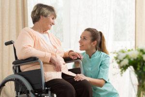 Elderly woman in wheelchair and hospice helper