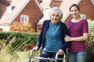 Daughter Helping Senior Mother To Use Walking Frame